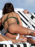 Claudia Galanti wearing an olive thong bikini on a beach in Miami from CelebMatrix