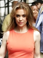 Alyssa Milano braless showing pokies in tight orange mini dress outside the studio in New York City
