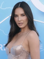 Olivia Munn busty in a low-cut silver sequined dress at The Rook premiere in LA