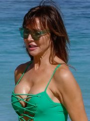 Lizzie Cundy shows off her big boobs in a plunging green swimsuit at the beach in Barbados