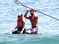 Avril Lavigne paddles out in open water in her Hot Topic bikini top