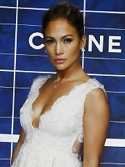Jennifer Lopez showing big cleavage in a white low cut mini dress at the Chanel fashion show