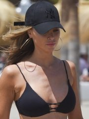 Lauren Pope busty showing pokies in tiny black bikini at the beach in Marbella