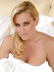 Jenny McCarthy shows her big boobs naked but covered in bed for a Christmas photoshoot