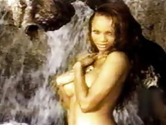 A young Tyra Banks covers her exposed titties while modeling next to a waterfall