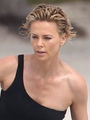 Charlize Theron jet skiing in black monokini during the photoshoot in Miami Beach
