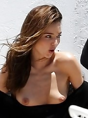 Miranda Kerr showing off her boobs downblouse while shooting in some black monokini at Miami Beach